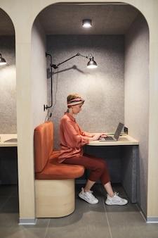 Портрет в полный рост татуированной молодой женщины, использующей ноутбук во время работы в будке кафе в офисе, копией пространства