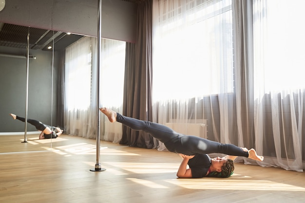 Full length side view portrait of sporty elegant woman in black clothes lying on her back and doing acrobatic element in pole dance studio