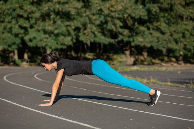 Full length side view of a pretty athletic girl on a plank position at the stadium