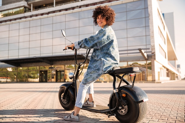 Full-length side view of smiling curly woman sitting on motorbike