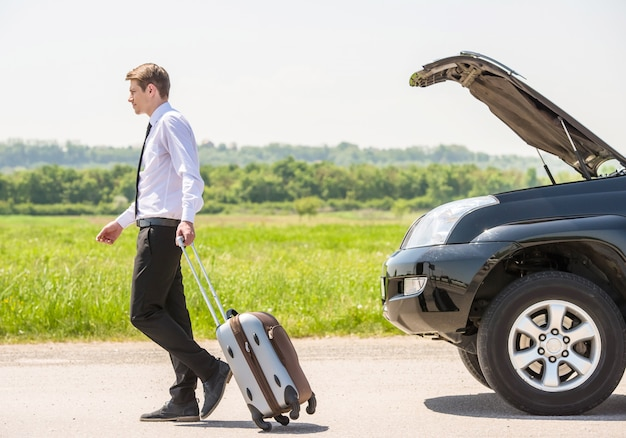 Full length side view of young businessman with suitcase.