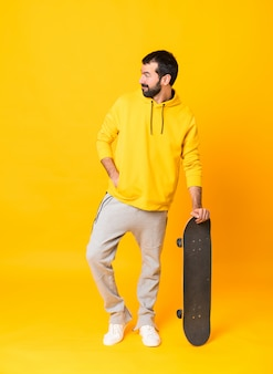 Full length  a skater man over isolated yellow wall