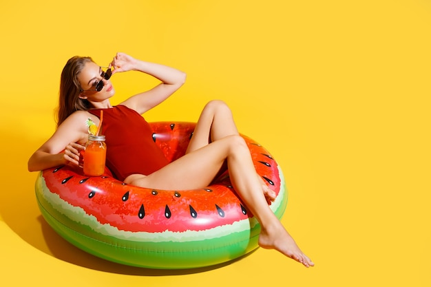 Full length slim girl wears red swimsuit sits on inflatable ring isolated on yellow background