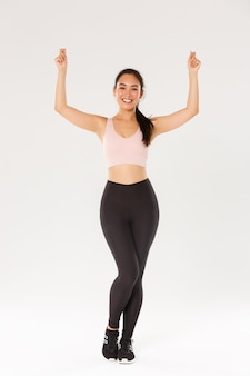 Full length of slim and healthy asian smiling girl workout, standing in sportswear and raising hands up as if holding sign or banner, advertise sports equipment or gym membership discounts.