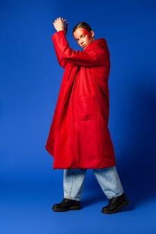 주머니에 손을 잡고 파란색 배경에 춤을 세련된 옷을 입은 전체 길이 슬림 여성