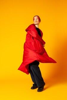Стройная женщина в полный рост в модном пальто oversize смотрит в сторону и кружится, танцуя на желтом фоне