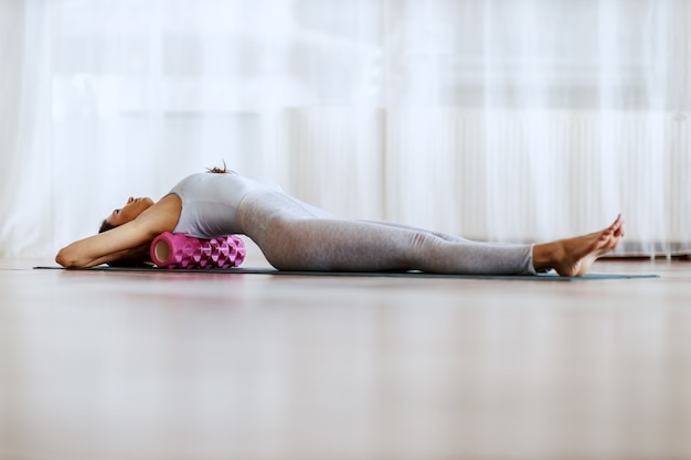 Full length of slim young woman lying on the backs and stretching it with roller.