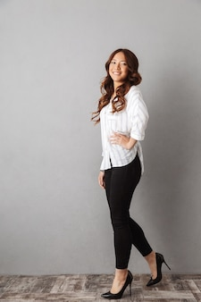 Full length of a smiling asian business woman standing, posing