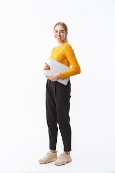Full length of a smiling attractive young blonde woman wearing sweater standing isolated over white wall, carrying laptop computer