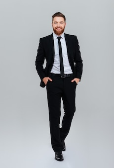 Full length smiling bearded business man in black suit with hands in pockets