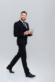Full length smiling bearded business man in suit moves with tablet computer
