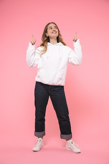 Full length smiling blonde woman wearing in casual clothes pointing and looking up over pink wall