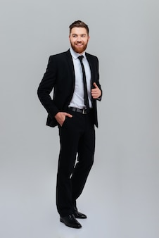 Full length smiling business man in black suit standing sideways with one hand in pocket isolated gray background