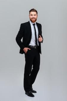 주머니에 한 손으로 옆으로 서있는 검은 양복에 전체 길이 웃는 비즈니스 남자 격리 된 회색 배경