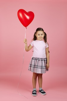 手に赤いハート型の風船とピンクのドレスで満足のいくフルレングスの笑顔の子供