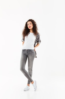 Full length smiling curly woman posing   over white wall