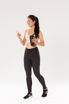 Full length of smiling fit and healthy female fitness coach, asian sportswoman checking water tracker reminder in smartphone, using application during workout in gym