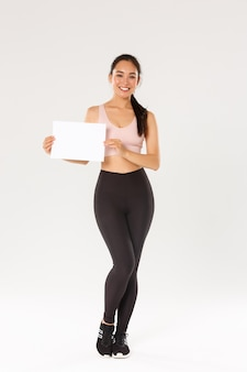 Full length of smiling good-looking asian brunette sportswoman, female athlete in sportswear showing sign on blank paper, advertising gym membership or workout equipment special price.