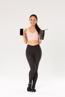 Full length of smiling good-looking asian fitness girl, sportswoman in activewear showing smartphone screen and water bottle, control drinking liquid with mobile application during training session