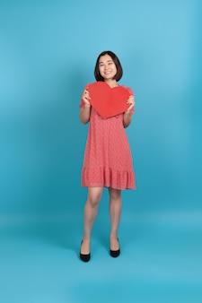 Полнометражная улыбающаяся счастливая молодая азиатская женщина в красном платье держит большое красное бумажное сердце