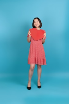 Full-length smiling happy young asian woman in red dress holding big red paper heart