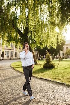 공식적인 마모에 전체 길이 웃는 남자, 화창한 날에 공원을 산책하고 스마트 폰으로 이야기