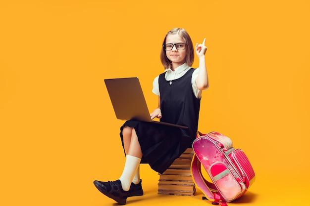 전체 길이의 웃는 학생은 노트북으로 책 더미에 앉아 집게 손가락 어린이 교육을 높입니다.