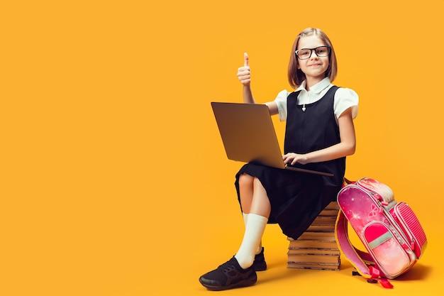 전체 길이의 웃는 학생은 노트북이 있는 책 더미에 앉아 아이들 교육을 엄지손가락으로 보여줍니다.
