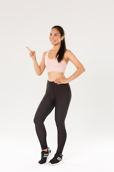 전체 길이 웃는 만족 된 여성 운동 선수, 그녀의 선택을 만드는 활성 착용에 아시아 피트니스 소녀, 가리키고 왼쪽 상단을보고, 훈련을 위해 체육관을 선택하십시오.