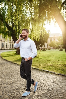 전체 길이 웃는 세련된 남자 30 대, 화창한 날 공원을 산책하고 모바일 통화
