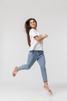 Full length of a smiling young woman casualy dressed jumping isolated on white