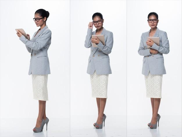 フルレングススナップフィギュア、アジアのビジネスウーマンスタンドフォーマルな適切なスーツスカートメガネハイヒールの靴、分離されたスタジオ照明白い背景、弁護士ボス行為ポーズ笑顔スマートルックデジタルタブレット