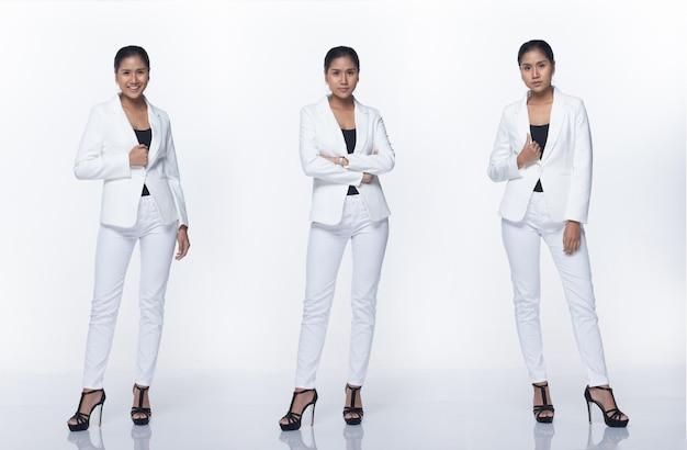フルレングスのスナップフィギュア、白いフォーマルなスーツのズボンと靴でアジアのビジネスウーマンスタンド、分離された白い背景のスタジオ照明、弁護士ボス行為ポーズ笑顔スマートルック