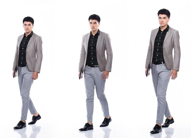 Полная длина оснастки, кавказский деловой человек стоит в костюме темно-зеленой рубашке, серых брюках и туфлях, у него уверенная прогулка, счастливая улыбка, сильная, коллажная группа на белом фоне, изолированные