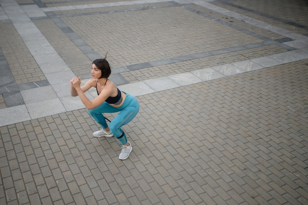 Full length of a sportswoman doing stretching exercise by a wall outdoors. fitness woman exercising by a wall. free time, spare time, leisure