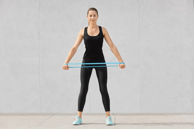 Full length sporty woman dressed in black sportsclothes, holds rubber resistance band, has workout at home, poses on grey. people, endurance, determination