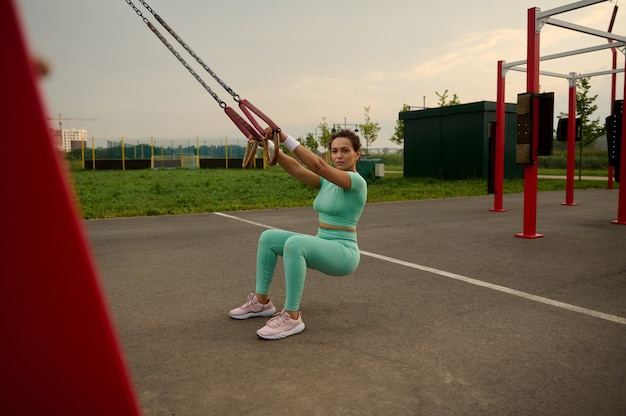Full length of sporty young athlete performing bodyweight squats with suspension straps on the outdoor sports field, enjoying early morning heavy workout. healthy lifestyle, fitness and sport concept