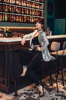 Foto d'archivio a tutta lunghezza di un modello brunetta di lusso estremamente alla moda con top corto, giacca scintillante d'argento, pantaloni neri e tacchi alti. modello in abito alla moda seduto su uno sgabello da bar in un club o in un bar.