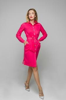 ボタンとベルトとスタイリッシュなハイヒールの明るいピンクのドレスで歩いている明るい口紅を持つゴージャスな女性の完全な長さのストックフォト。カメラ目線のポケットに手を入れて歩くモデル。