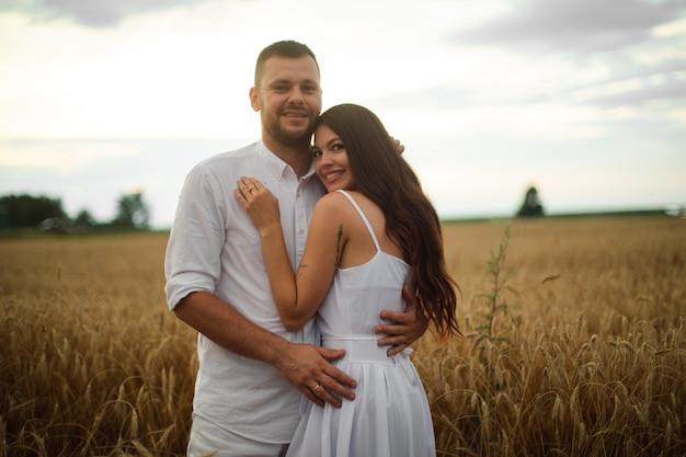 日没時に麦畑で抱き締める白い服を着たロマンチックなカップルの完全な長さのストックフォト。