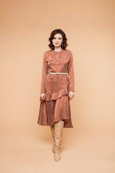 Полная длина фото привлекательной брюнетки кавказской женщины в элегантном коралловом платье