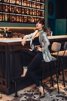 Фотография в полный рост чрезвычайно модной роскошной брюнетки в укороченном топе, блестящей серебряной куртке, черных брюках и на высоких каблуках. модель в модном наряде сидит на барном стуле в клубе или баре.