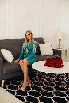 赤いバラとテーブルの横にある灰色のモダンなソファに座っているベージュのかかとと緑のフォーマルなドレスで魅力的な金髪の白人の大人の女性の完全な長さのストックフォト。