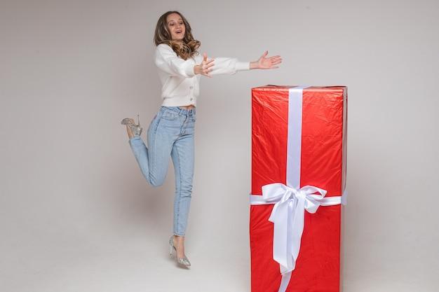 白い背景の上の白い弓と赤い紙の巨大な贈り物と腕を伸ばしてかかとで陽気なジャンプの女の子の完全な長さのストックフォト。
