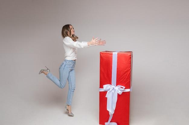 Фото в полный рост веселой прыгающей девушки на каблуках с вытянутыми руками с гигантским подарком в красной бумаге с белым бантом на белой стене
