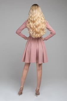 腰に腕を保持しているベージュのハイヒールとトレンディなライトピンクのドレスを着ているゴージャスなブロンドの女性の完全な長さのストックフォトの肖像画。背面図。モデリング。背景を分離します。スタジオショット。