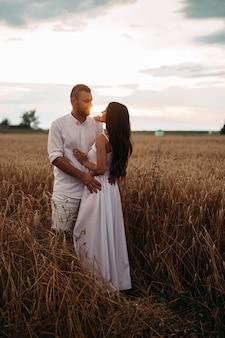 Foto d'archivio a tutta lunghezza di una coppia romantica in abiti bianchi che si abbraccia nel campo di grano al tramonto.