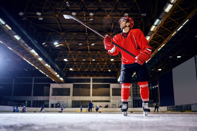 Full length of strong hockey player in uniform with helmet swinging with stick and preparing to shoot on the goal.