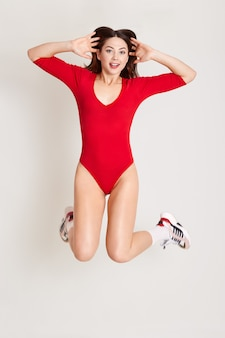 Full length studio photo of attractive woman jumping in air with arms extended