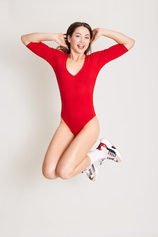 Full length studio photo of attractive woman jumping in air with arms on her head